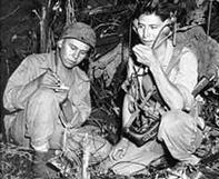 Cpl. Henry Bake, Jr., és Pfc. George H. Kirk, 1943. decemberében a sűrű dzsungelban egy hordozható adóvevővel.